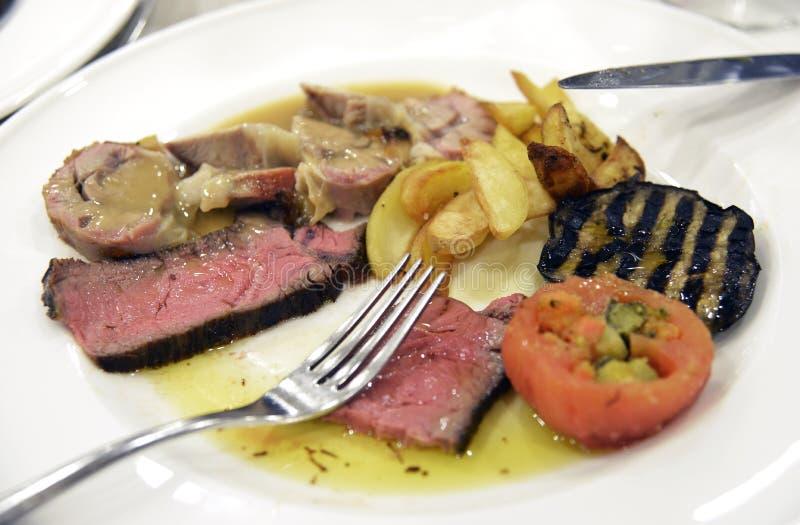Platta av skivat kött med auberginetomater och potatisar royaltyfria bilder