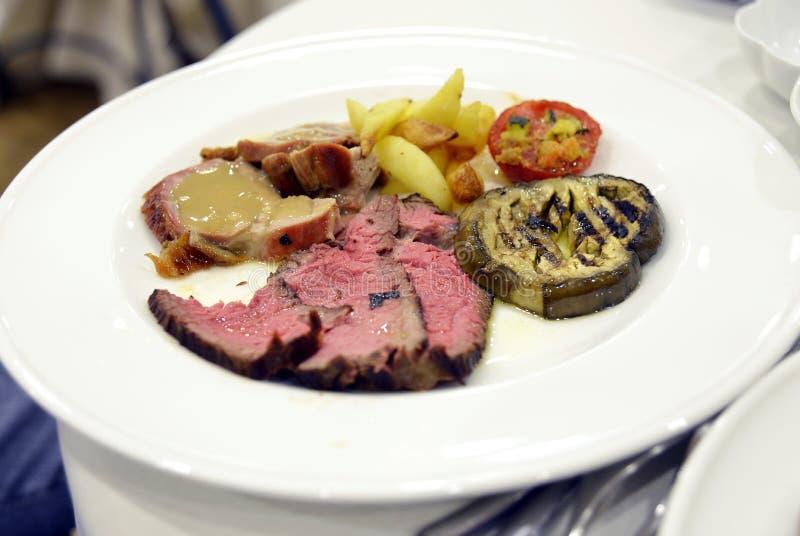 Platta av skivat kött med auberginetomater och potatisar royaltyfri bild
