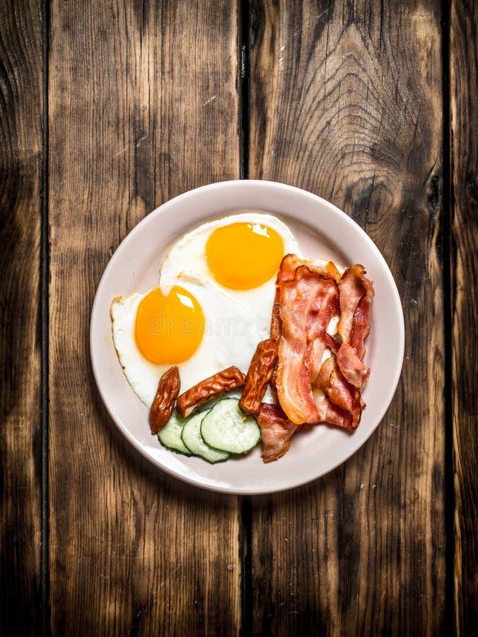 Platta av stekte ägg, bacon, gurkan och rökte korvar fotografering för bildbyråer