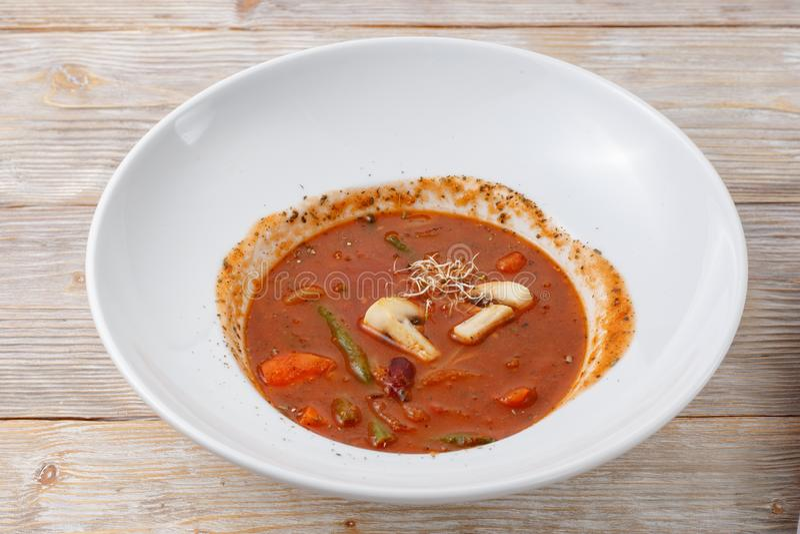 Platta av tomatsoppa med grönsaker och mikrogräsplan på träbakgrund royaltyfria bilder