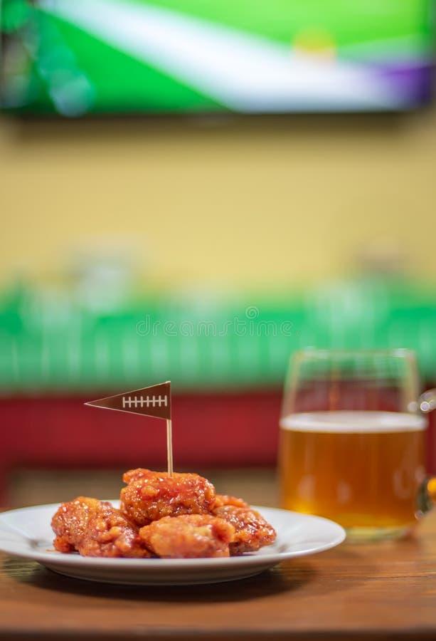 Platta av utan ben varma vingar och öl med sportar på TV i backgr fotografering för bildbyråer