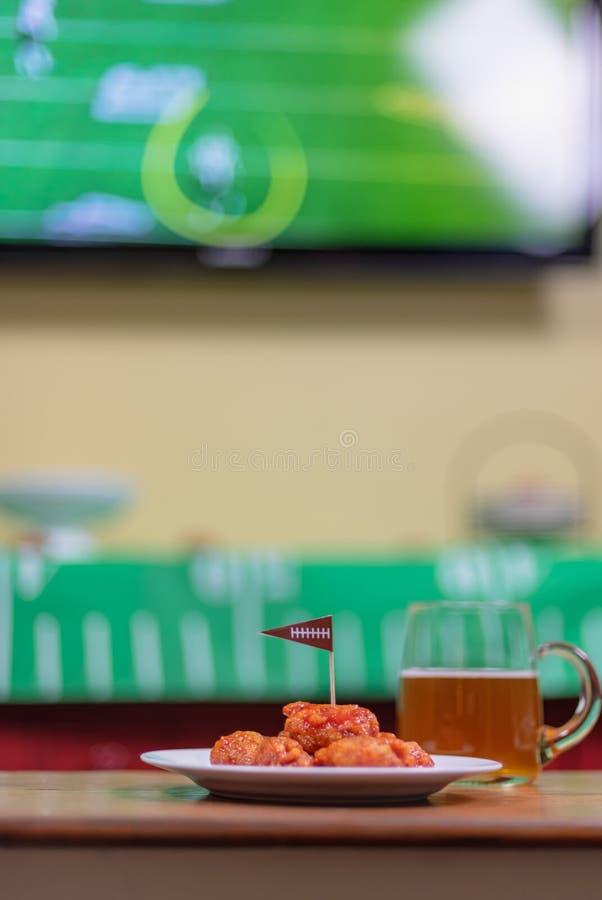 Platta av utan ben varma vingar och öl med sportar på TV i backgr royaltyfria foton