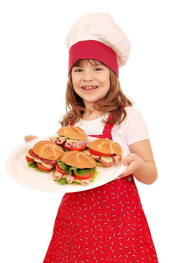 Platta för liten flickakockhåll med smörgåsar arkivbilder