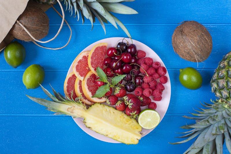 Platta för ny frukt på livlig blå bakgrund - ananas, kokosnöt, limefrukt Bästa sikt från ovannämnd fast utgift tropisk strandlivs royaltyfri bild