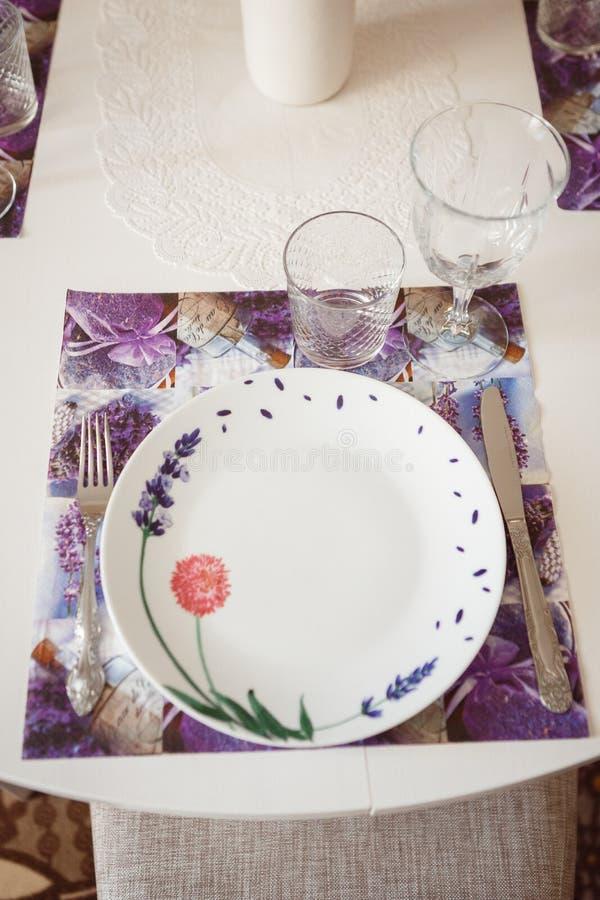 Platta, gaffel och exponeringsglas på en violett servett arkivbild