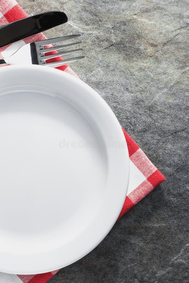 Platta, kniv och gaffel på servett fotografering för bildbyråer