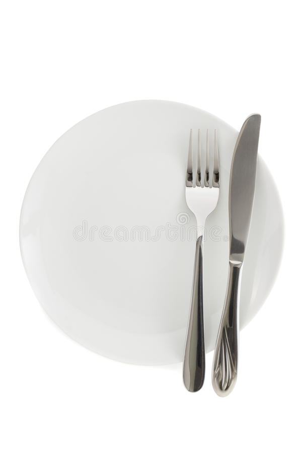Platta, kniv och gaffel på vit royaltyfria foton