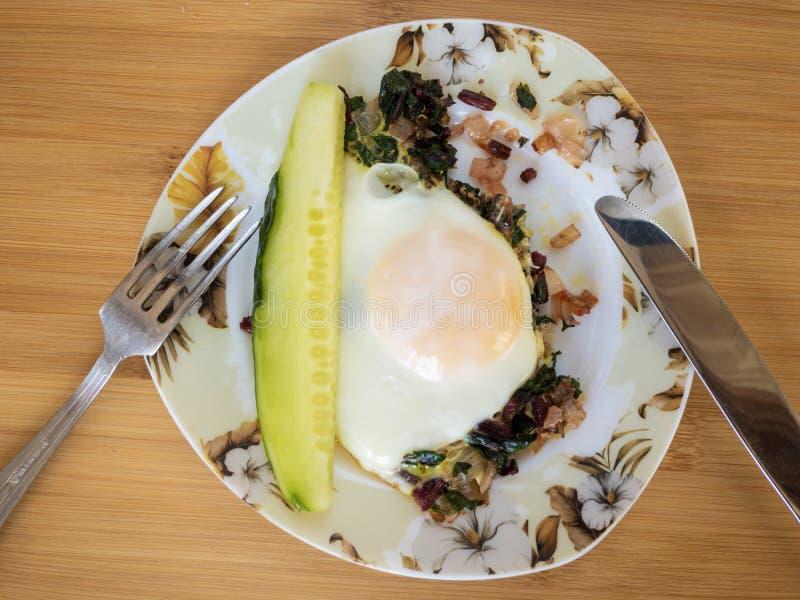 Platta med ägget som stekas på löken och foderbetan, skiva av gurkan, gaffel och kniv fotografering för bildbyråer