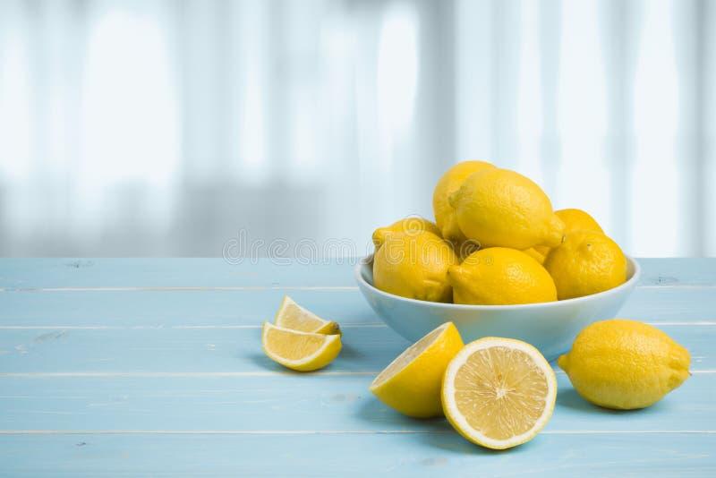 Platta med citroner på den blåa trätabellen över abstrakt bakgrund royaltyfria foton