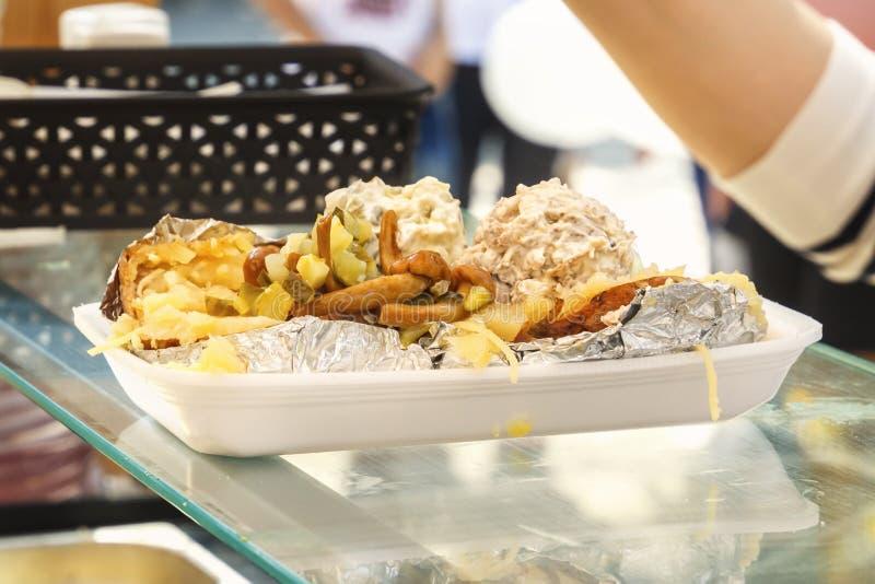 Platta med läcker gatamat - bakade potatisar med sås, champinjoner och grönsaker C royaltyfria bilder