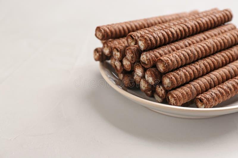 Platta med läckra chokladrånrullar på den vita tabellen, utrymme för text Söt mat arkivfoto