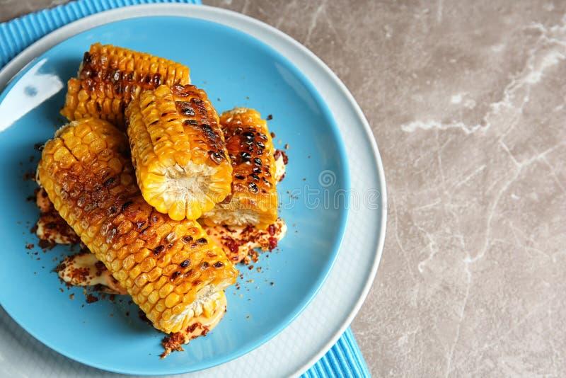 Platta med läckra grillade havremajskolvar och kryddor på tabellen, bästa sikt royaltyfri fotografi