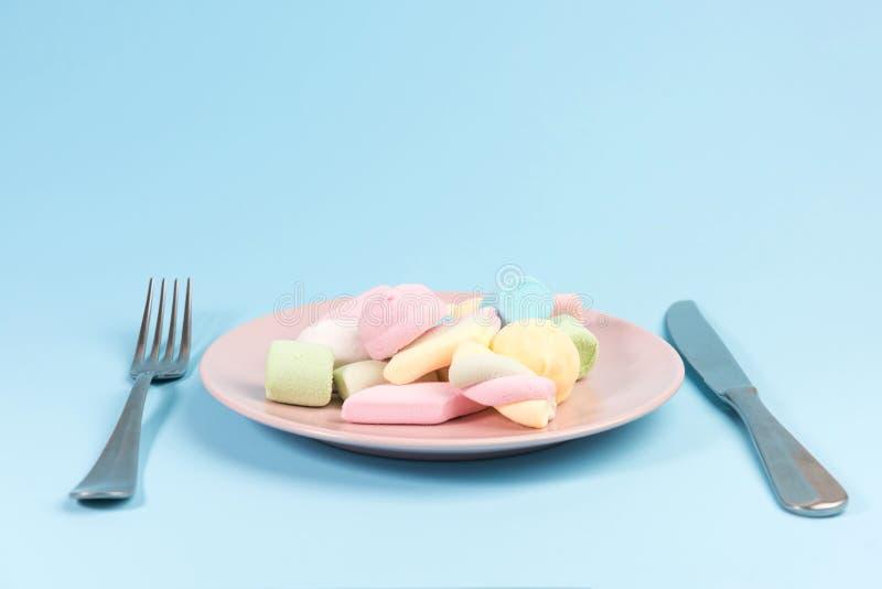 Platta med marshmallowen, gaffel, kniv som isoleras på blått royaltyfria foton