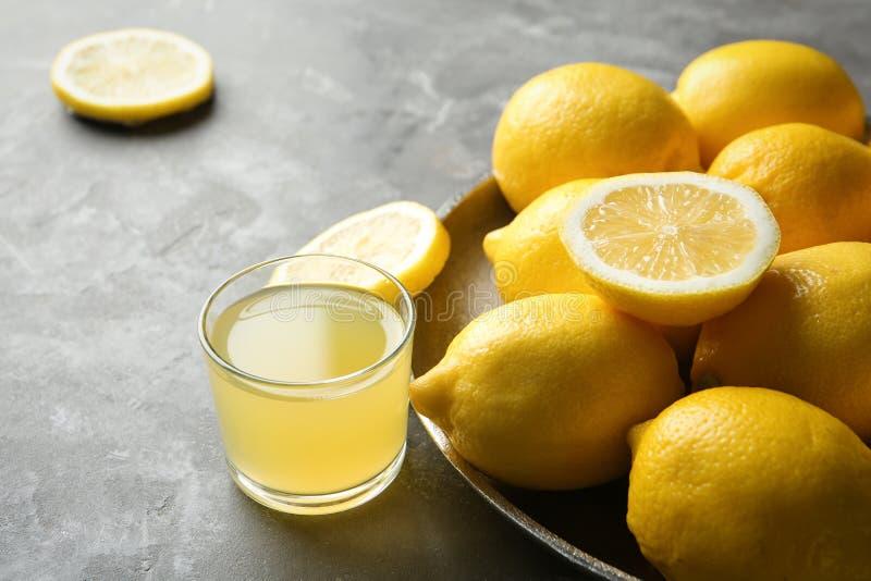 Platta med mogna citroner och exponeringsglas av ny fruktsaft royaltyfria foton