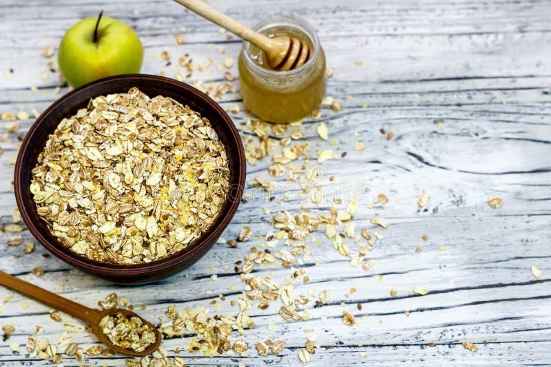 Platta med mysli på en träbakgrund nära äpplen och honung arkivbild