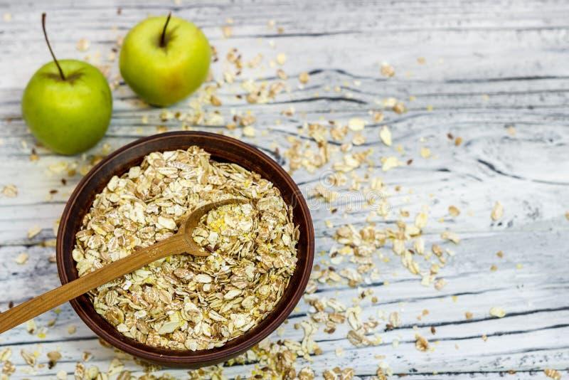 Platta med mysli på en träbakgrund nära äpplen och honung fotografering för bildbyråer