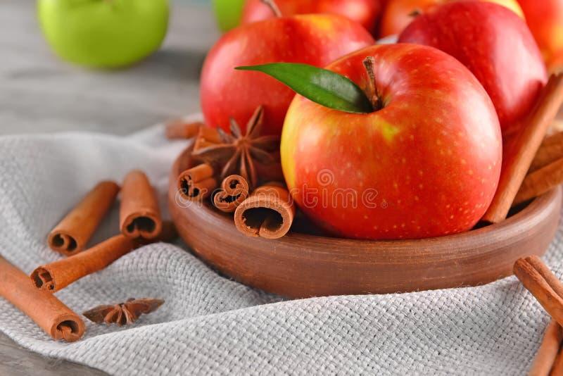 Platta med nya äpplen och kanelbruna pinnar på tabellen arkivfoton
