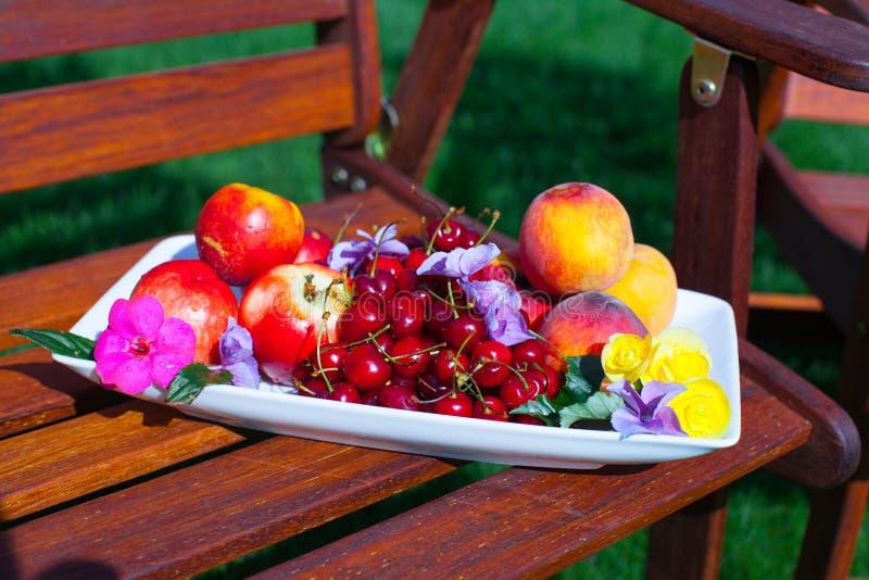 Platta med nya frukter och blommor på trä arkivfoto