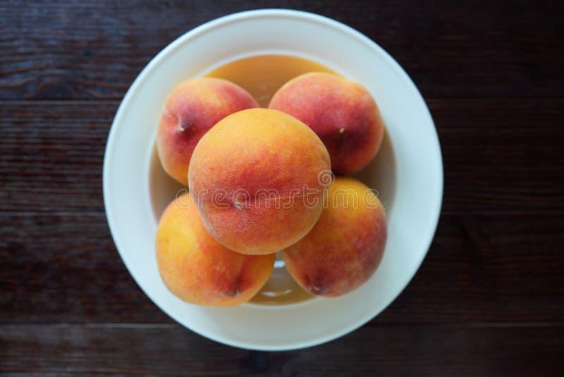 Platta med nya saftiga persikor royaltyfria foton