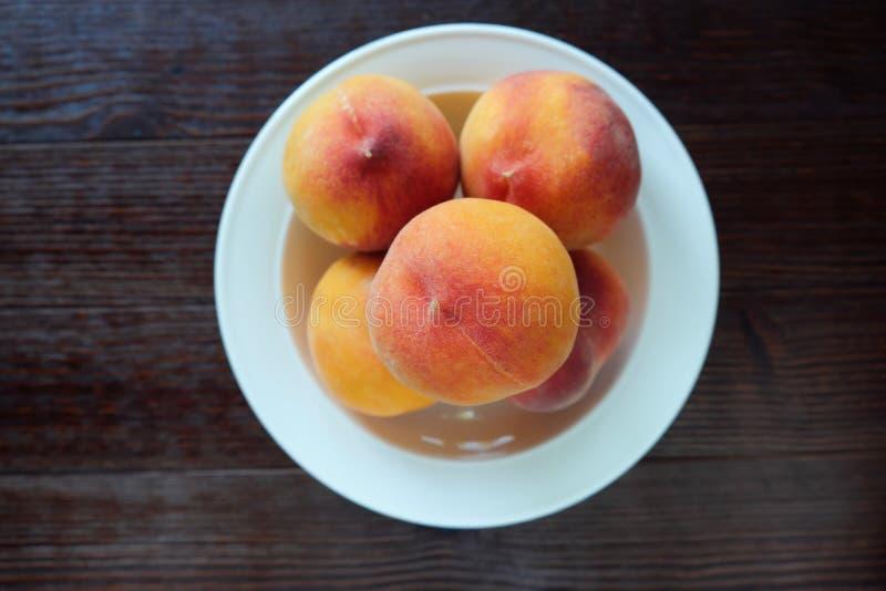 Platta med nya saftiga persikor royaltyfri foto