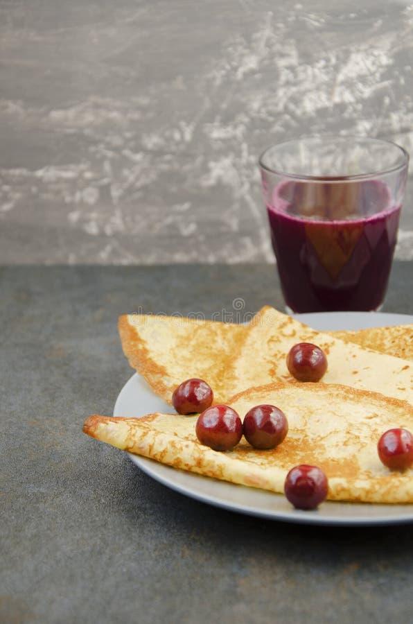 Platta med pannkakor och fruktsaft på den gråa tabellen Skjuten lodlinje royaltyfria bilder