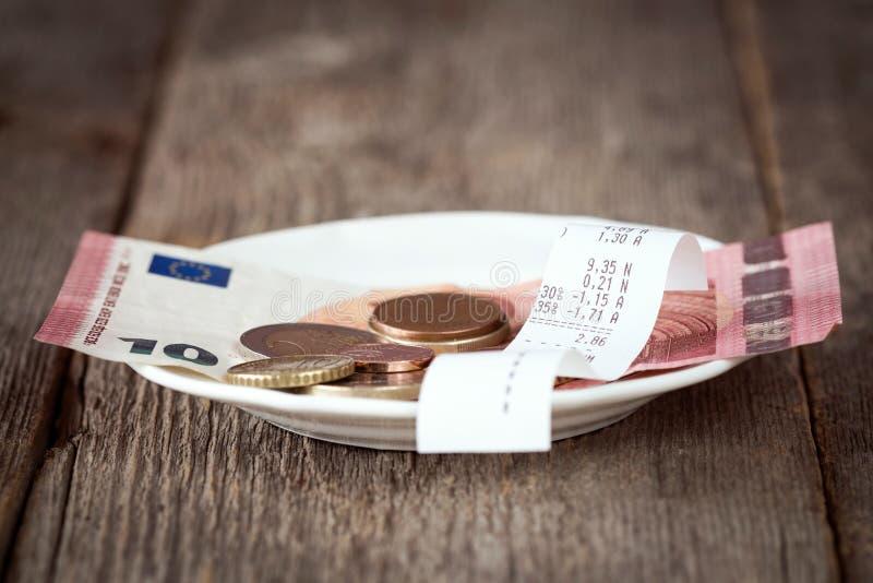 Platta med räkningen, pengar och spetsar arkivbild