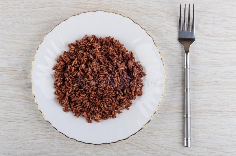 Platta med röda kokta ris, gaffel på tabellen Top beskådar royaltyfri foto