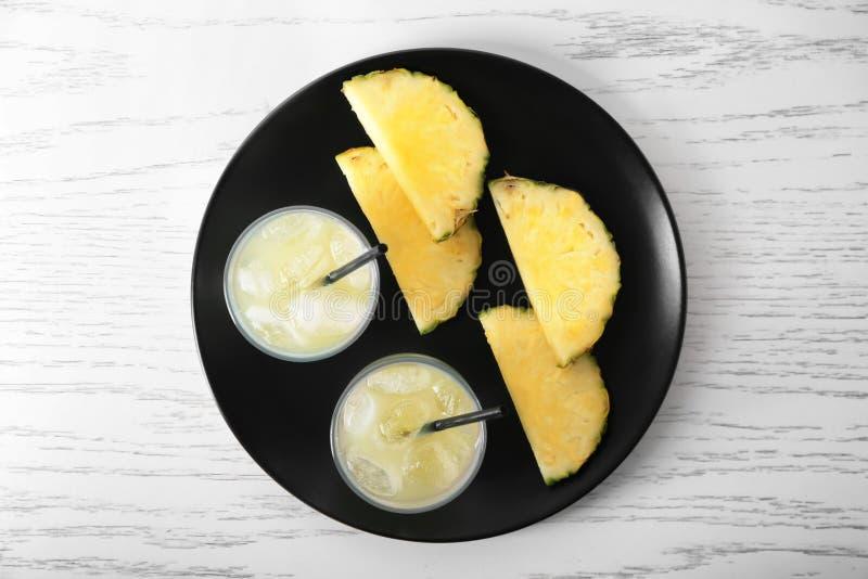 Platta med skivade ananas och exponeringsglas av ny fruktsaft på den vita trätabellen royaltyfria bilder