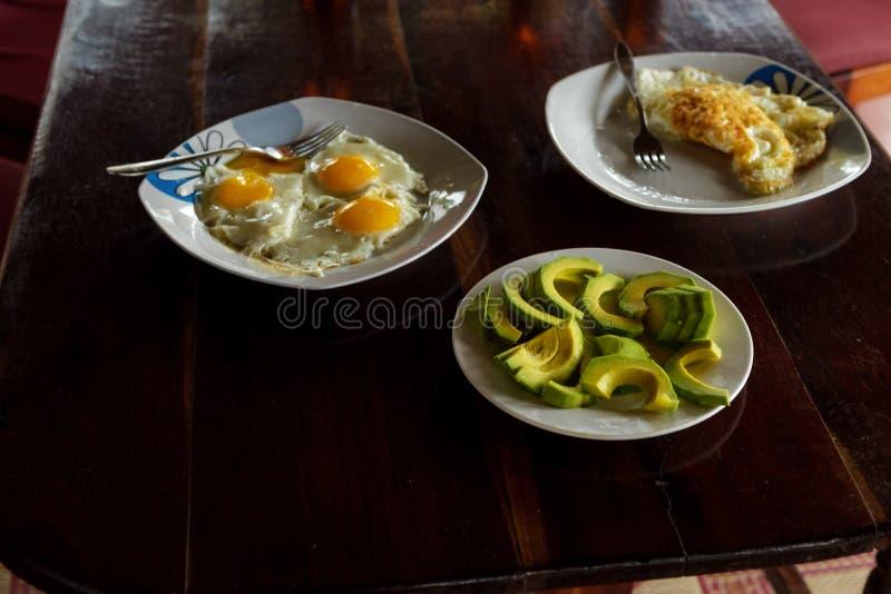 Platta med skivor av avokadot, stekte ägg och förvanskade ägg royaltyfri bild