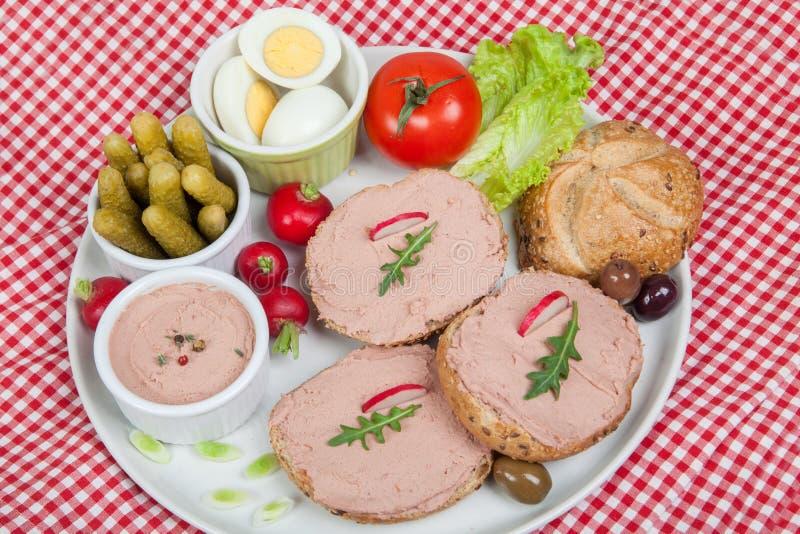 Platta med skivor av bröd med hem- gjord pate som dekoreras med grönsaker royaltyfri bild