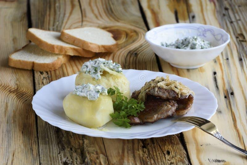 Platta med stekt griskött och kokta potatisar arkivbilder