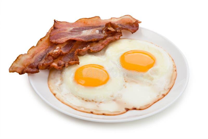 Platta med stekte ägg, bacon som isoleras på vit bakgrund royaltyfria bilder