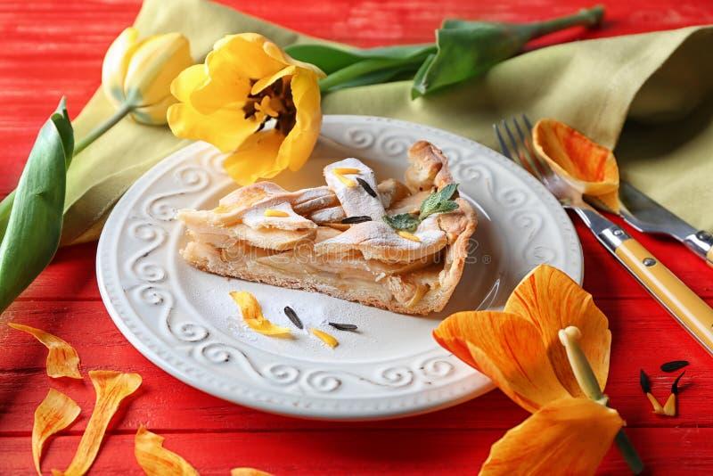 Platta med stycket av den smakliga hemlagade äppelpajen på färgträtabellen arkivfoto