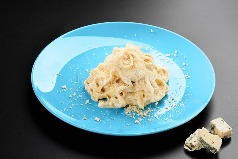 Plattan av italiensk Penne pasta med en krämig välsmakande sås och basilika för formaggio tjänade som i en blå maträttsvartmeny royaltyfria bilder