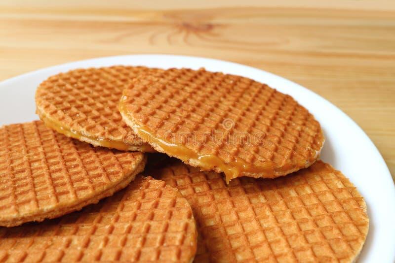 Plattan av Stroopwafel kakor, smakliga holländska traditionella sötsaker tjänade som på trätabellen royaltyfri bild