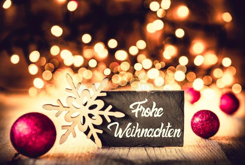 Plattan kalligrafi Frohe Weihnachten betyder glad jul, purpurfärgade bollar arkivbild