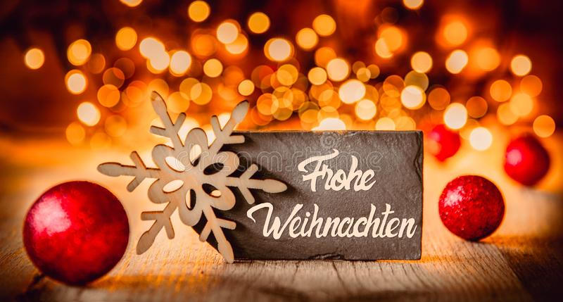 Plattan kalligrafi Frohe Weihnachten betyder glad jul, röda bollar arkivfoto
