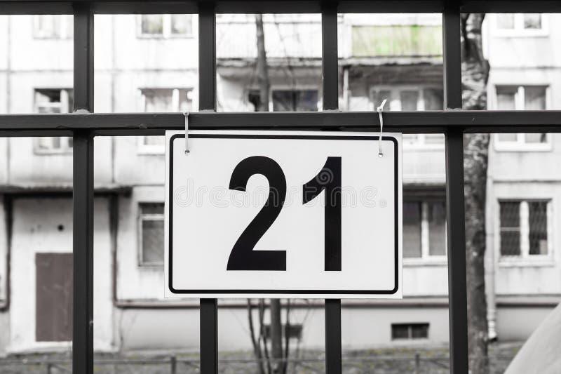 Plattan med nummer 21 hänger på parkeringsplatsen royaltyfri fotografi