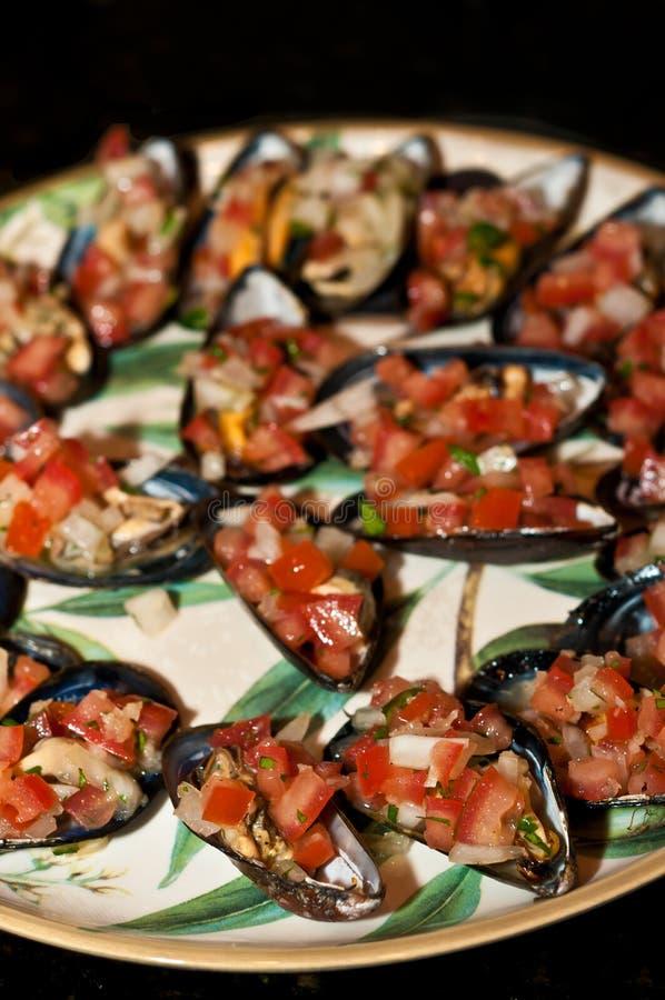 Platte der gedämpften und abgekühlten Miesmuschel mit gehackter Zwiebel und Tomate stockfotografie