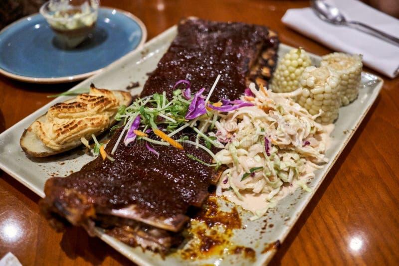 Platte der köstlichen und saftigen Schweinefleischrippe mit Ofenkartoffeln, Salat und Körnern lizenzfreie stockfotografie