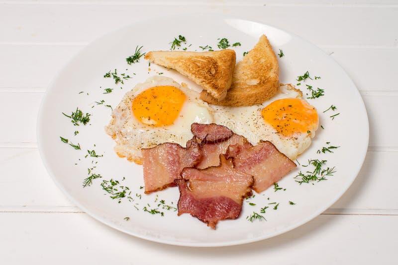 Platte des Frühstücks mit den Spiegeleiern, Speck und Toast lokalisiert auf weißem Hintergrund lizenzfreie stockbilder