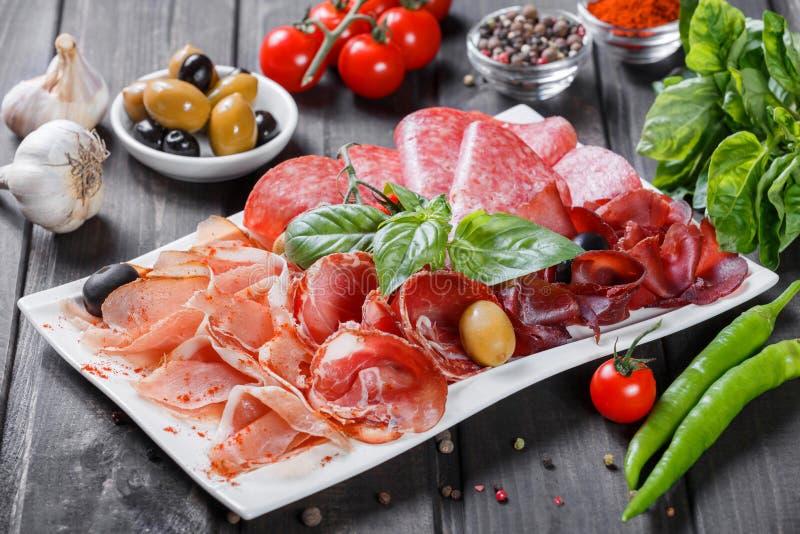 Platte des kalten Fleisches der Antipastoservierplatte mit Prosciutto, Scheiben Schinken, Salami, verziert mit Basilikum und Oliv lizenzfreie stockfotos
