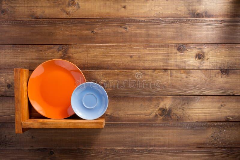 Platte am hölzernen Regal der Küche an der Wand stockbild