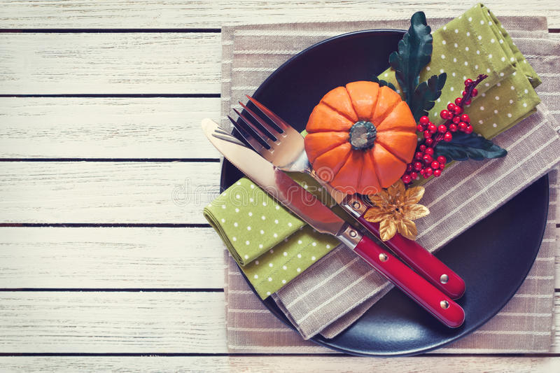 Platte, Löffel, Gabel, Messer und Platte auf Rotem Kreuz-spinnen Ginghamfliesetischdecke lizenzfreie stockbilder