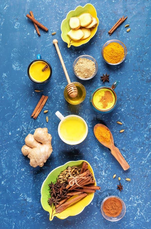 Platte lay-out van kopjes goudturmere melk en ingrediënten voor het koken ervan op blauwe achtergrond Verticale foto royalty-vrije stock fotografie