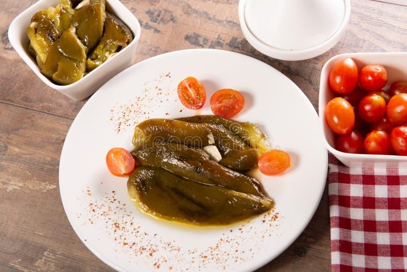 Platte mit den gr?nen Paprikas mariniert im Oliven?l lizenzfreie stockbilder
