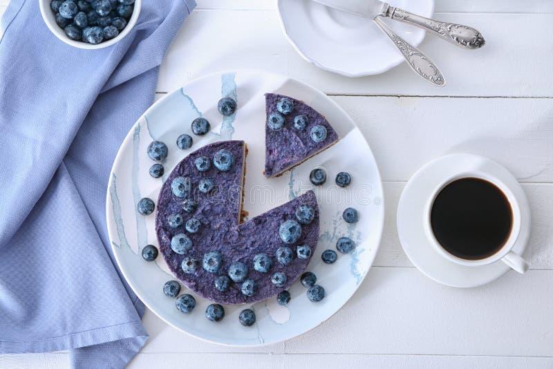 Platte mit geschmackvollem Blaubeerkäsekuchen und -Tasse Kaffee auf weißer Tabelle lizenzfreie stockfotos