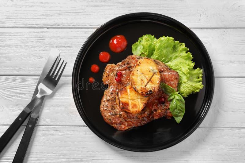 Platte mit geschmackvollem gegrilltem Fleisch und Kartoffeln auf Tabelle lizenzfreie stockfotos