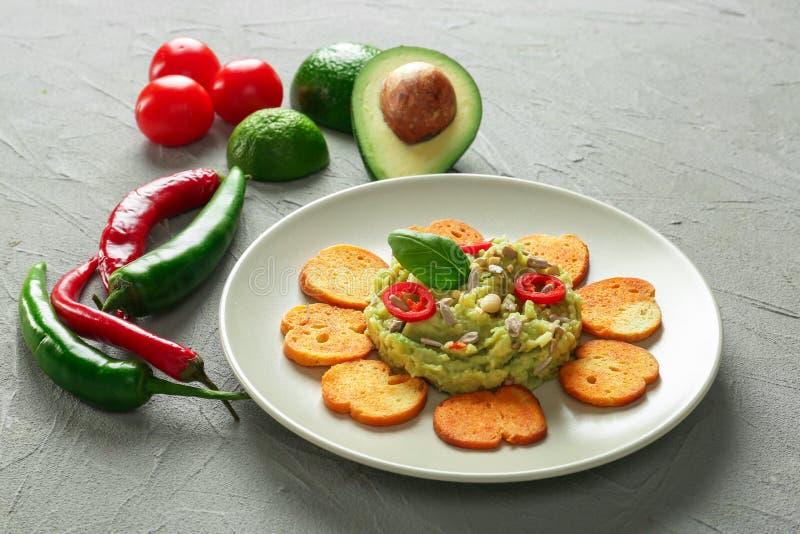 Platte mit geschmackvollem Guacamolen, Zwiebacken und Frischgemüse auf strukturiertem Hintergrund stockfoto