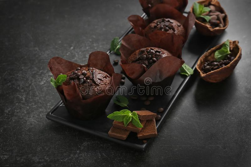 Platte mit geschmackvollen Schokoladenmuffins auf grauer Tabelle stockfoto